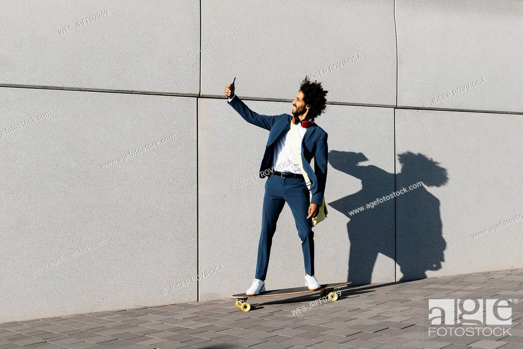 Stock Photo: Young businessman riding skateboard along a wall taking a selfie.