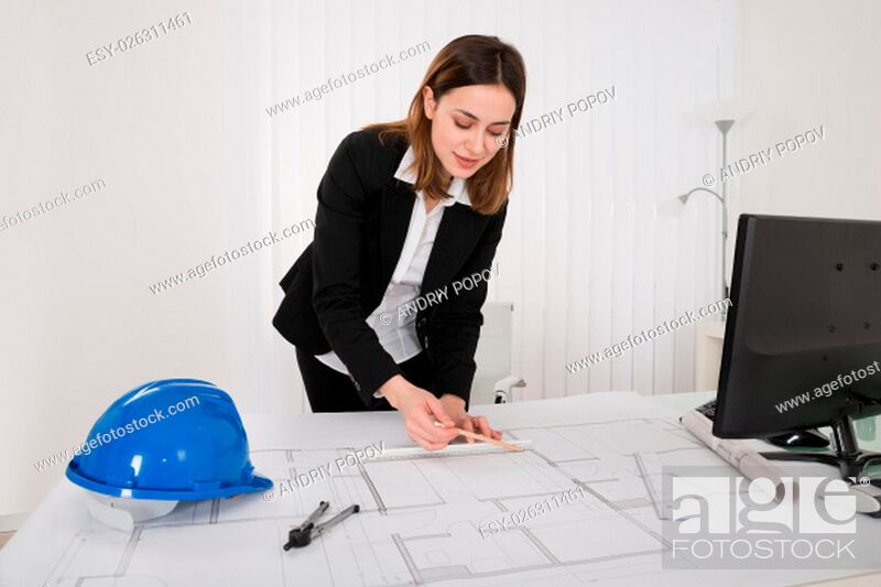 Stock Photo: Young Happy Female Architect Working On Blueprint In Office.