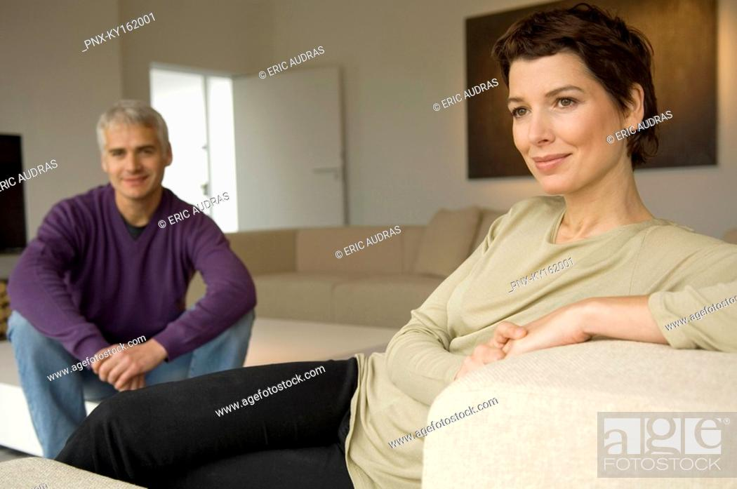 Stock Photo: Mid adult woman and a mature man sitting in a living room.
