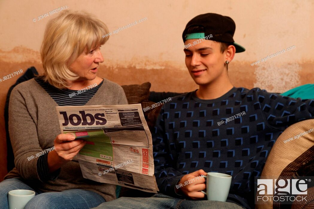 Imagen: Teenager with grandmother looking at newspaper for jobs.