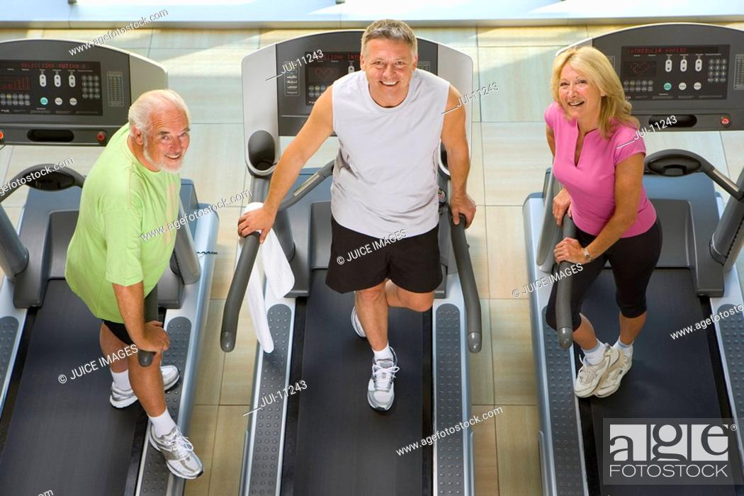 Stock Photo: Senior couple and man on treadmills, smiling, portrait, elevated view.