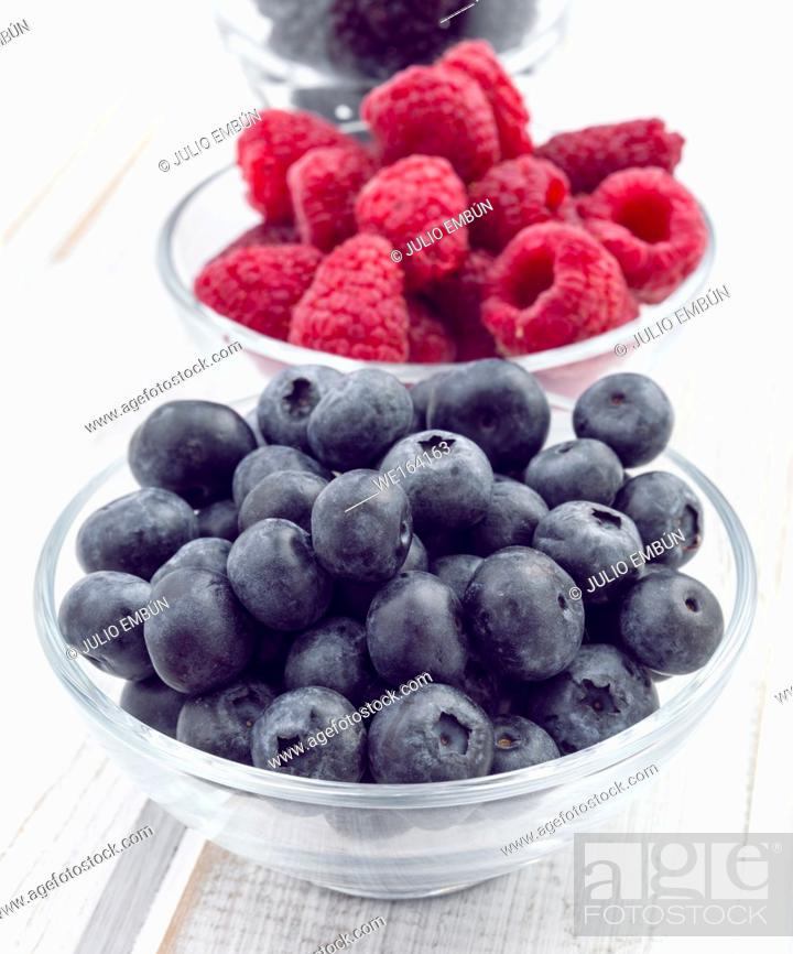 Photo de stock: bowl of blueberries and currants on wooden board.