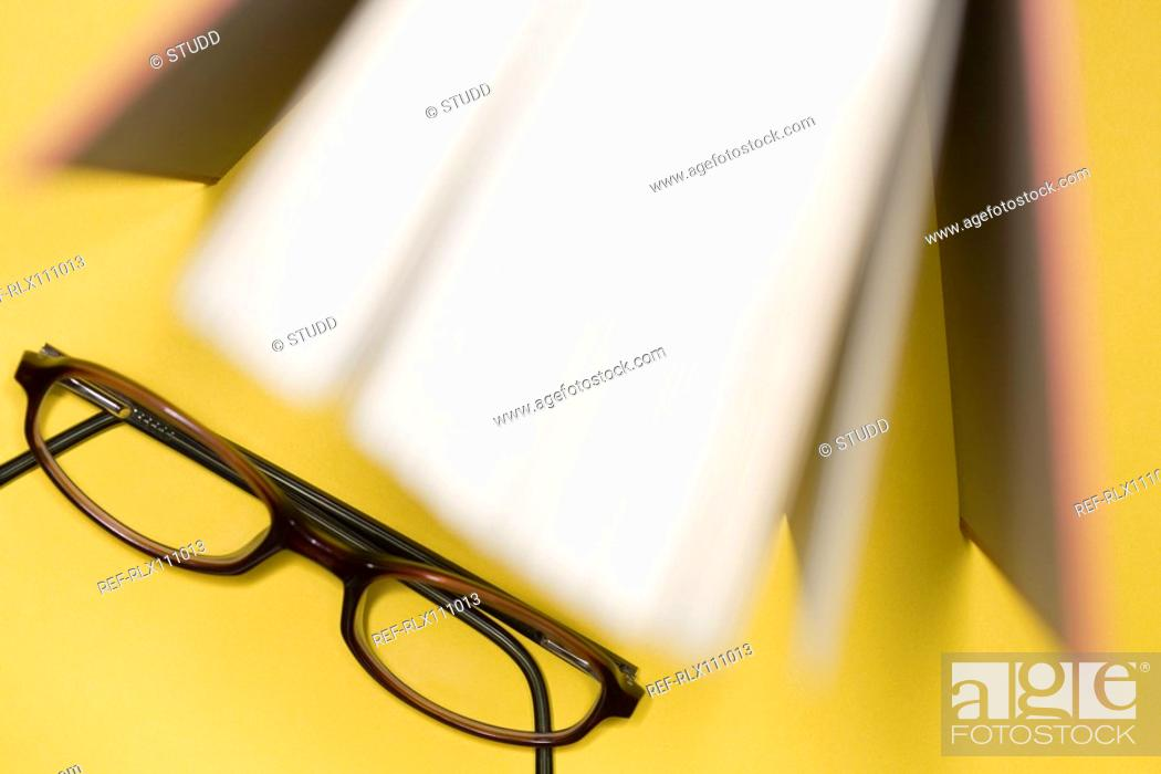 Stock Photo: Close up of open book and reading glasses.