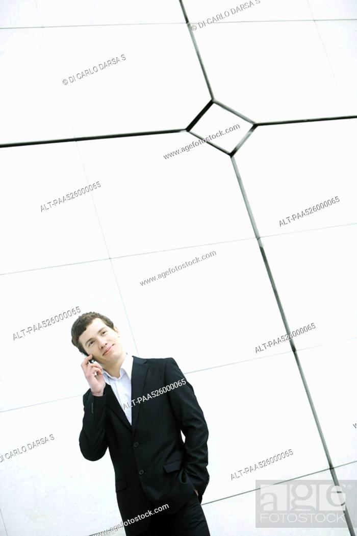 Photo de stock: Businessman using cell phone, hand in pocket, casually standing by wall.