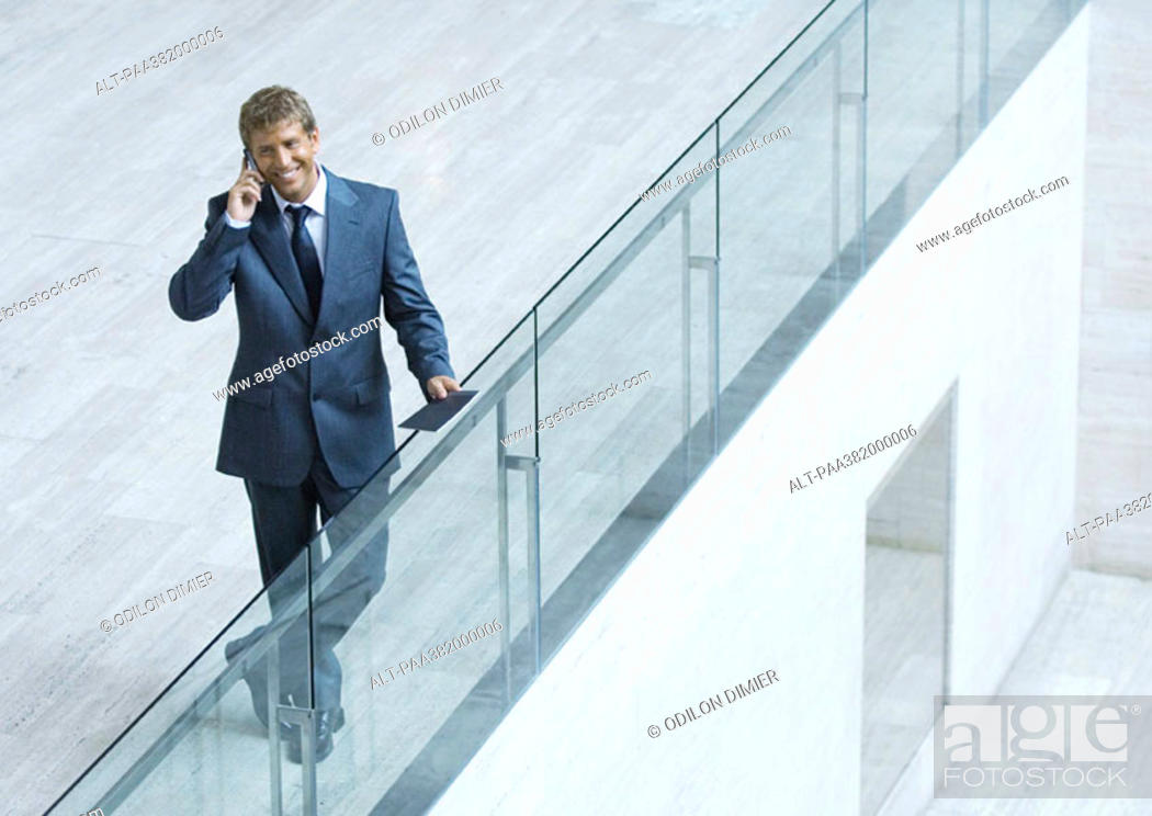 Stock Photo: Businessman leaning on railing, using cell phone, high angle view.