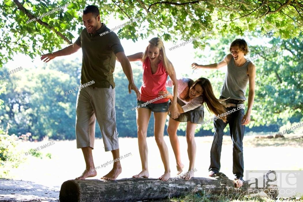 Stock Photo: Four young people balancing on a log in a park.