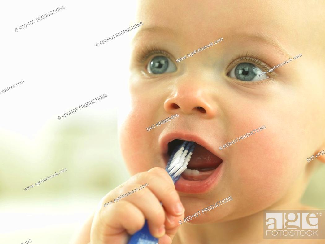 Stock Photo: Baby's face close up with toothbrush in mouth.