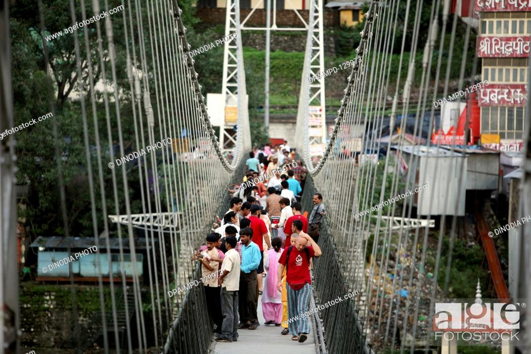Stock Photo: People from across the Lakshman jhula situated over Ganga River at Rishikesh  ;  Uttaranchal ; India.