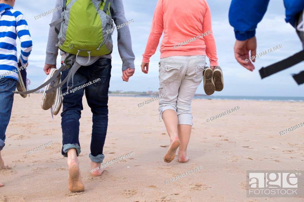 Stock Photo: Family of four walking along a beach barefoot. They are wearing warm casual clothing and only their bodies can be seen.