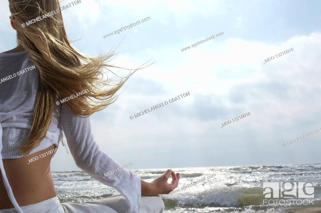 Stock Photo: Young woman meditating on beach facing ocean back view.