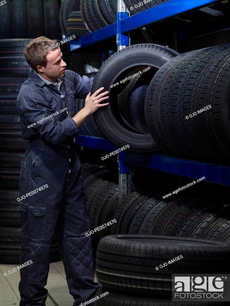 Stock Photo: Mechanic removing tire from rack.