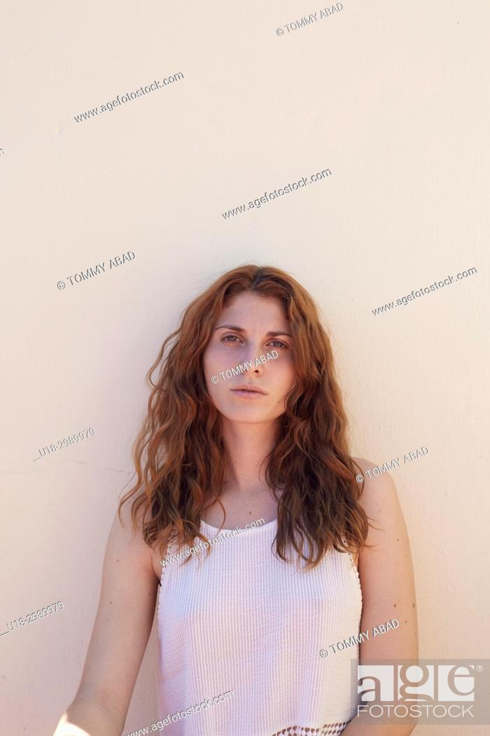 Imagen: Half-length portrait of young redhead woman leaning against a white wall.