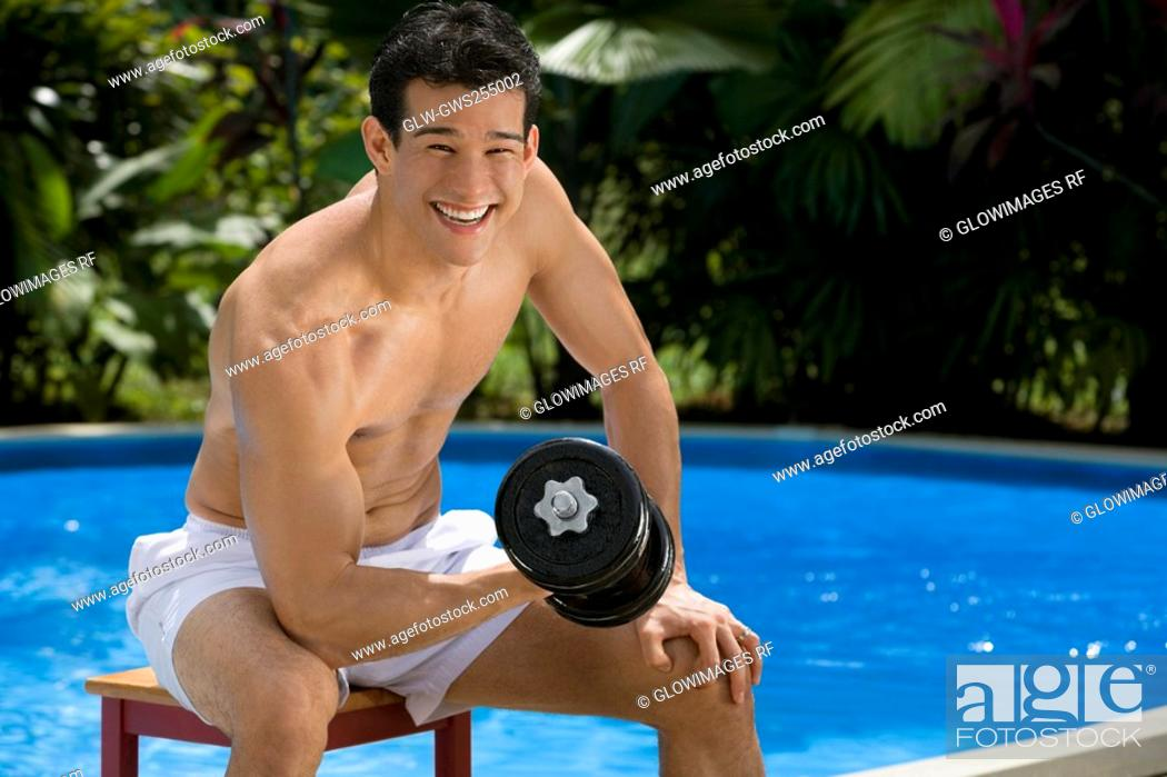 Stock Photo: Portrait of a young man exercising with a dumbbell at the poolside.