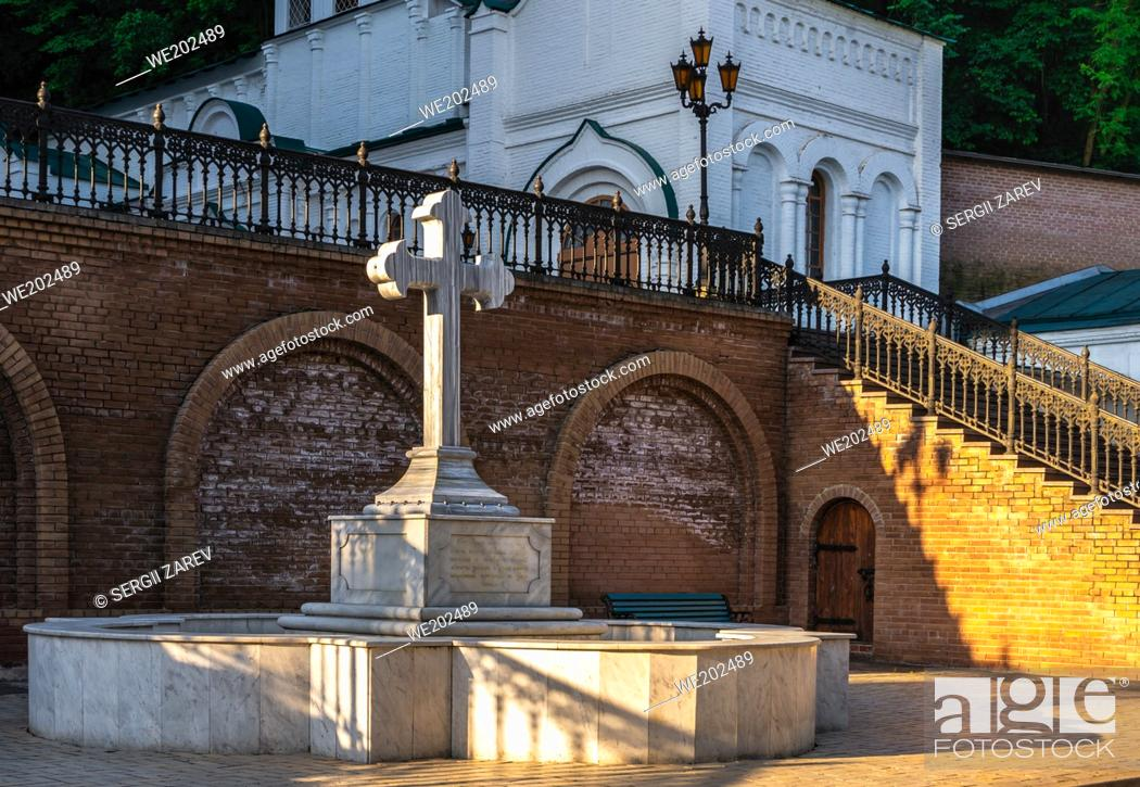 Stock Photo: Svyatogorsk, Ukraine 07. 16. 2020. Memorial cross at the entrance to the Assumption Cathedral in the Svyatogorsk Lavra on a sunny summer morning.