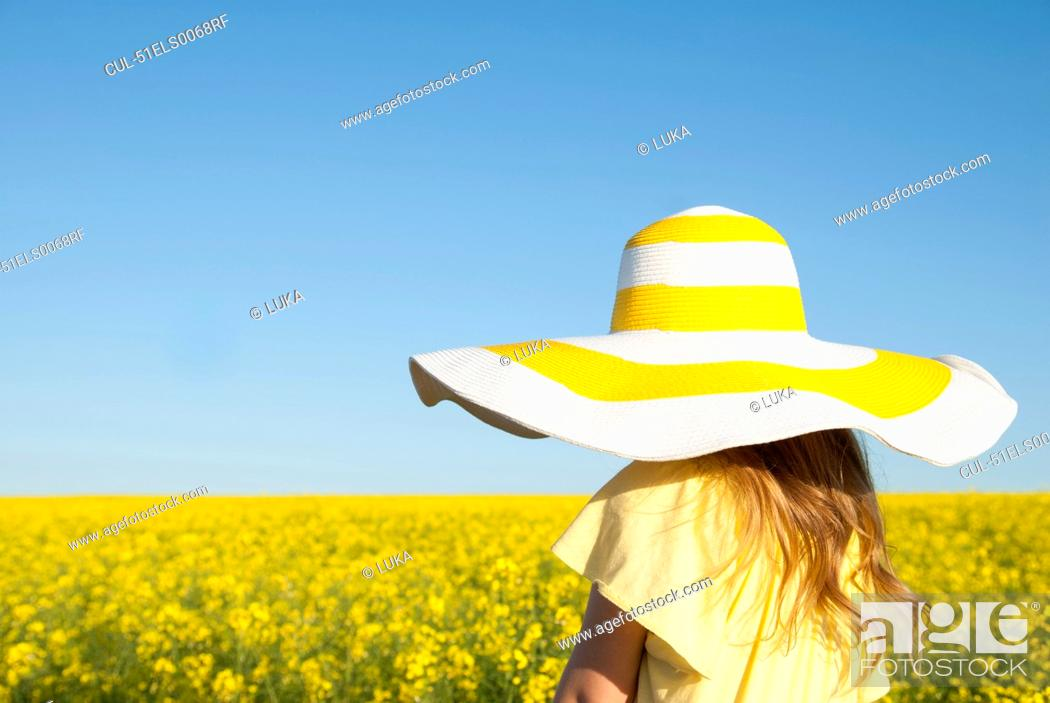 Stock Photo: Girl wearing sun hat outdoors.