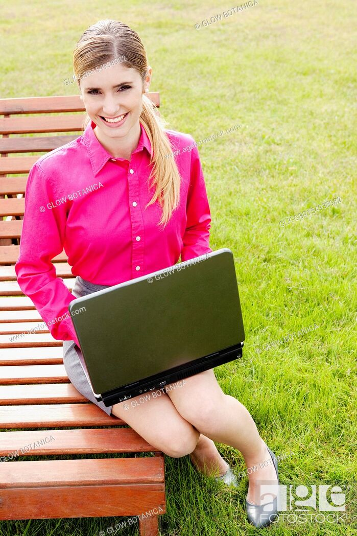 Stock Photo: Businesswoman using a laptop in a field.
