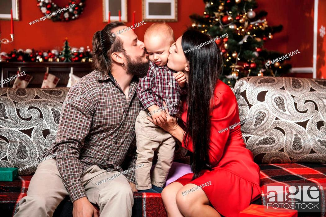 Stock Photo: Christmas family portrait in home holiday living room, kid and parents on sofa, decorate house with Xmas tree and gifts.