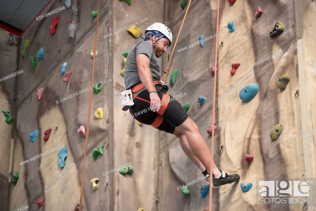 Stock Photo: Man climber on artificial climbing wall. Sport concept.