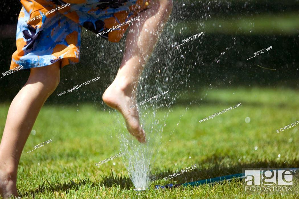 Stock Photo: Boy, 5, jumping over lawn sprinkler. Boise, Idaho. USA.