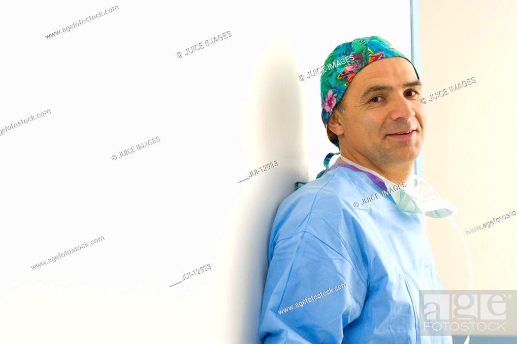Stock Photo: Portrait of surgeon by wall, smiling.