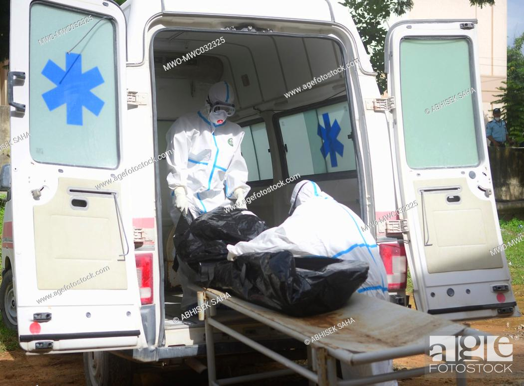 Stock Photo: A person has died due to the coronavirus. Medical staff wearing Personal Protective Equipment (PPE) kits are taking the dead body for cremation.