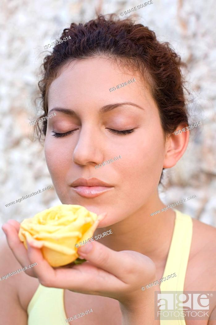 Stock Photo: Woman smelling a rose.