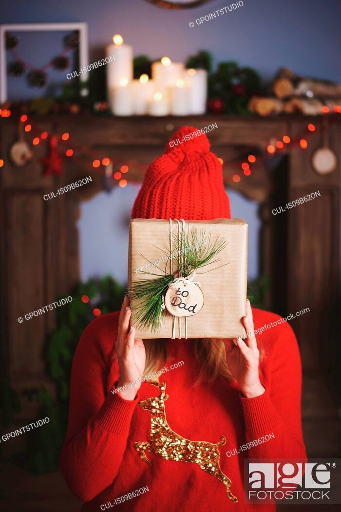 Stock Photo: Woman holding christmas present in front of face.