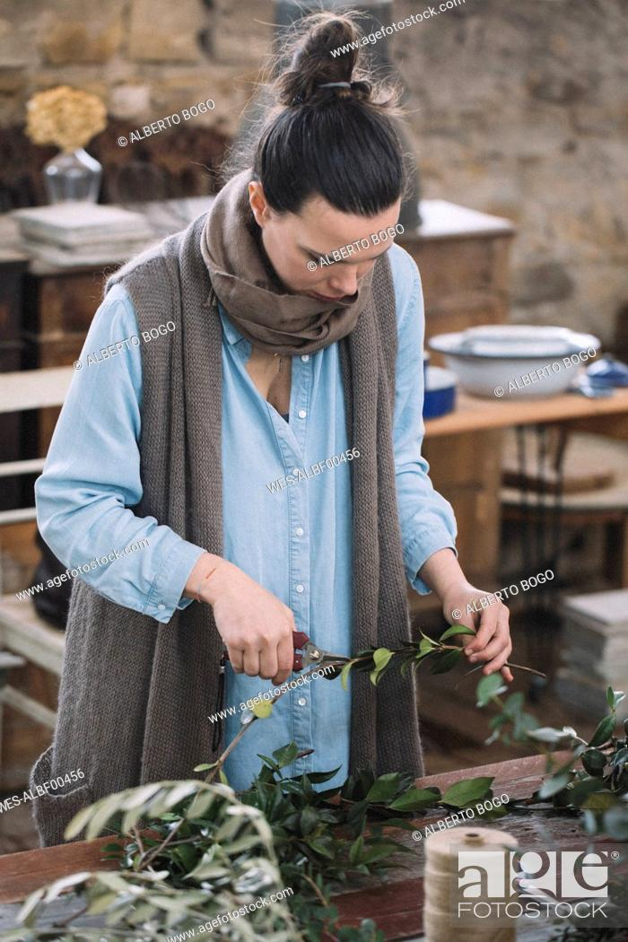 Stock Photo: Woman arranging twigs.