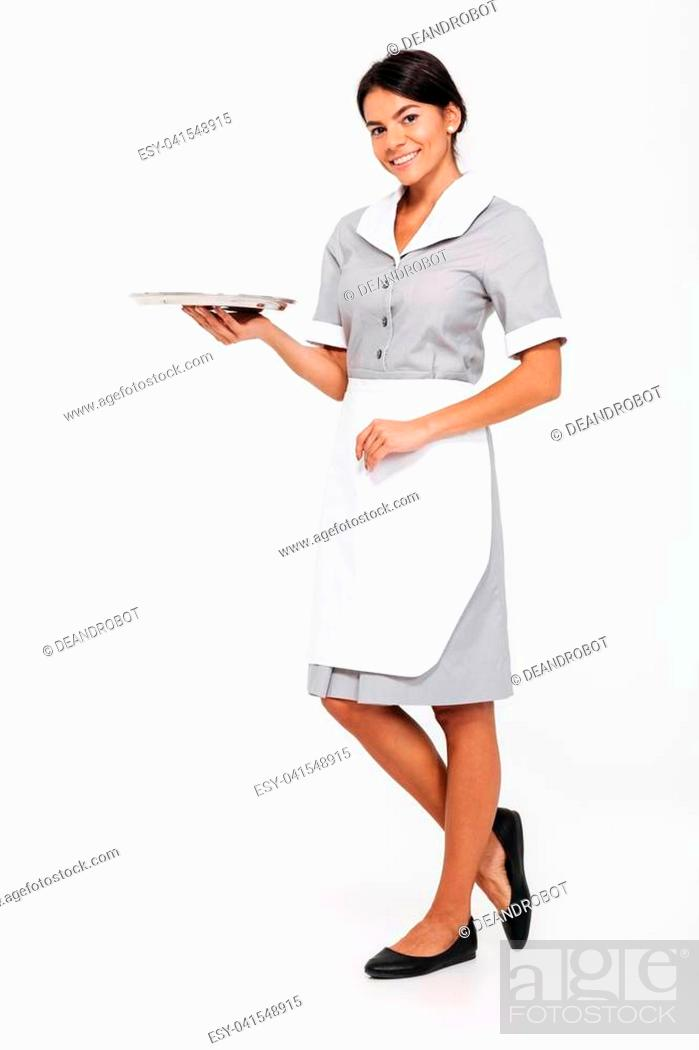 Photo de stock: Full length photo of young attractive woman in uniform holding metal tray with empty sign card while standing and looking at camera.