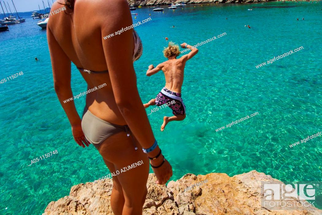 Stock Photo: Young boy jumping into sea. Cala Salada beach. Santa Agnés de Corona. Ibiza. Balearic Islands. Spain.