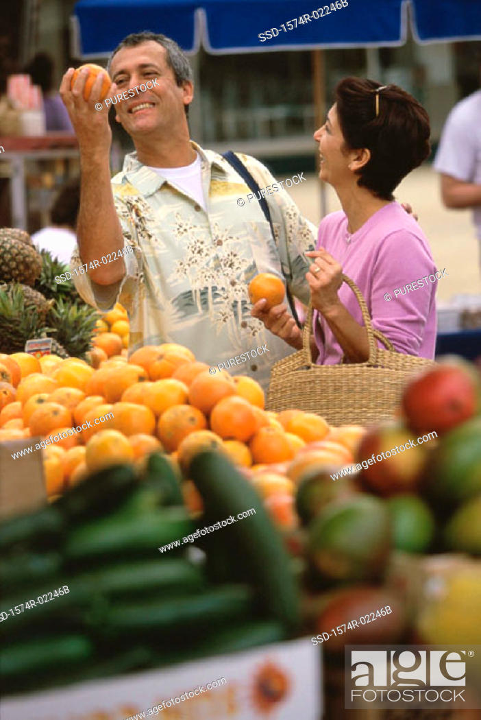 Stock Photo: Mature couple picking oranges from shop in a market.