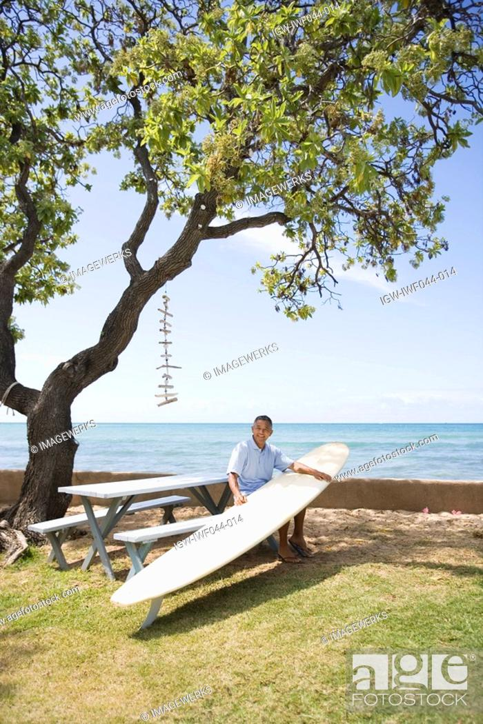 Stock Photo: Mature man sitting on bench with surfboard.