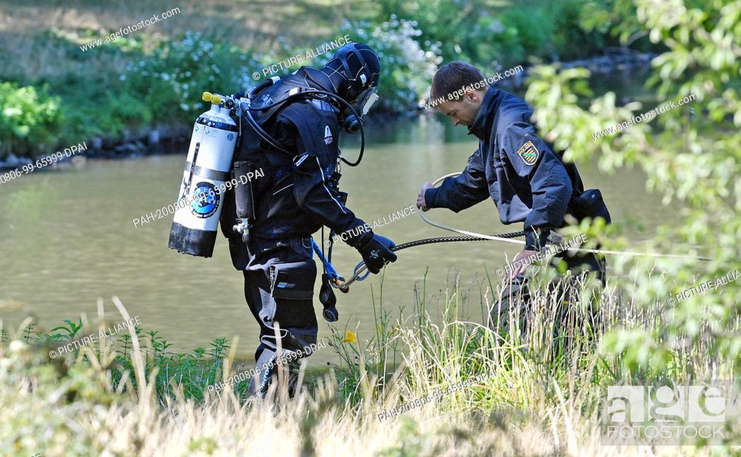 Stock Photo: 06 August 2020, Saxony, Leipzig: An officer of the diving group of the police puts on his equipment at the island pond in Clara-Zetkin-Park.