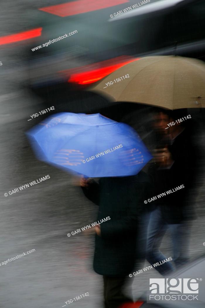 Stock Photo: person with umbrella crossing road in rain.