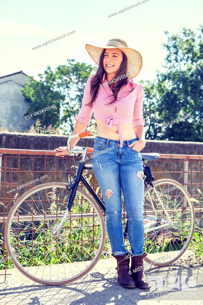 Photo de stock: pretty young woman on bike in a country road.