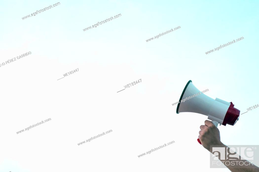 Stock Photo: Arm entering in the image and a hand holds a megaphone with a space to dispose of the according interest.