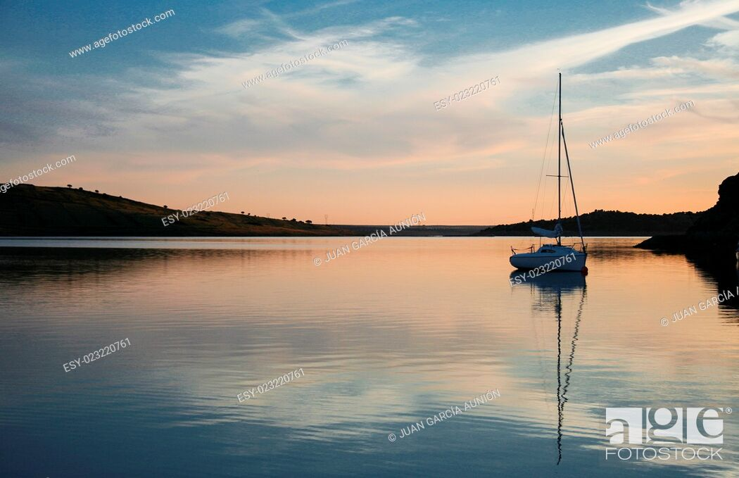 Imagen: Sailboat anchored in the middle of Alange Reservoir, Spain. Sunset hour.