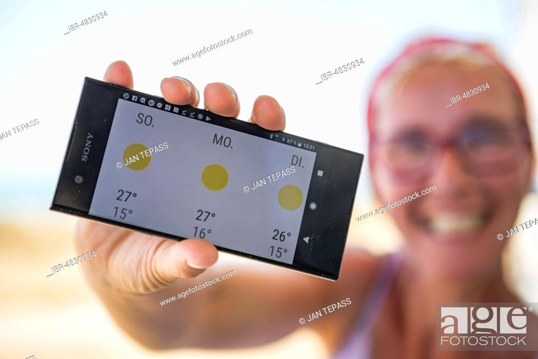 Stock Photo: Laughing woman on the beach happy about sunny weather in the weather forecast on her smartphone, Normandie, France.