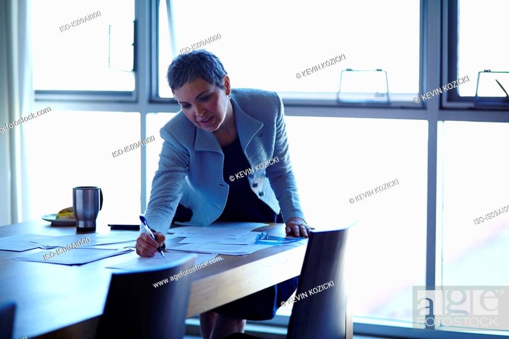 Stock Photo: Mature businesswoman at conference table checking papers.