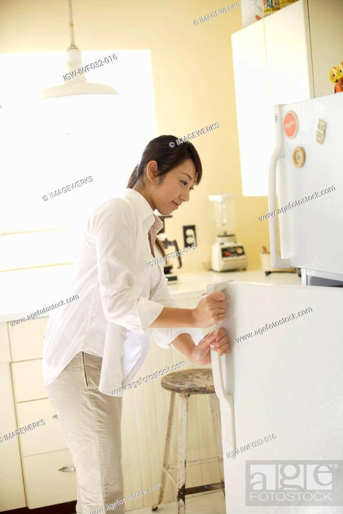 Stock Photo: A young woman opening refrigerator in kitchen.