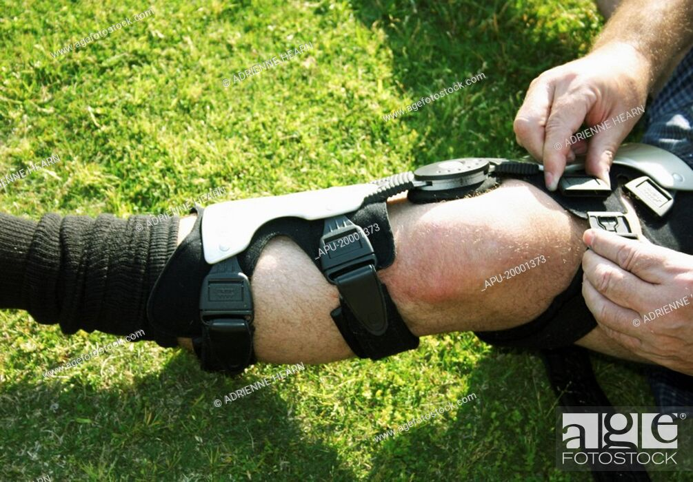 Stock Photo: Football player adjust knee brace before playing game.