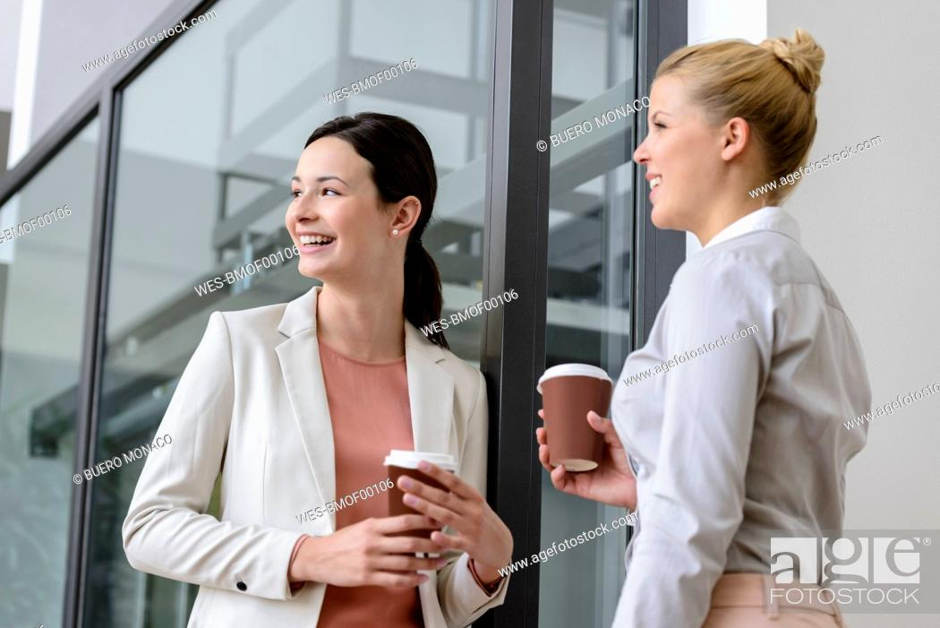 Stock Photo: Two smiling businesswomen having coffee break outside office building.