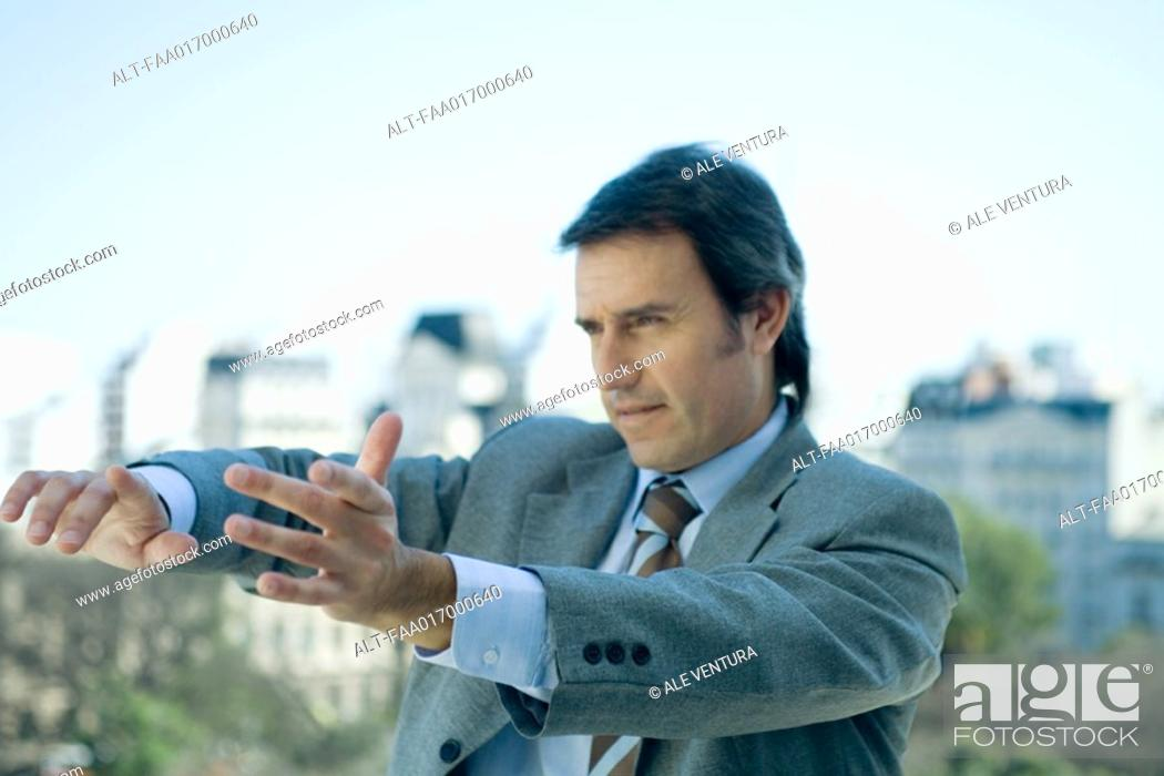 Stock Photo: Businessman holding arms out in front of him and pointing, looking out of frame.