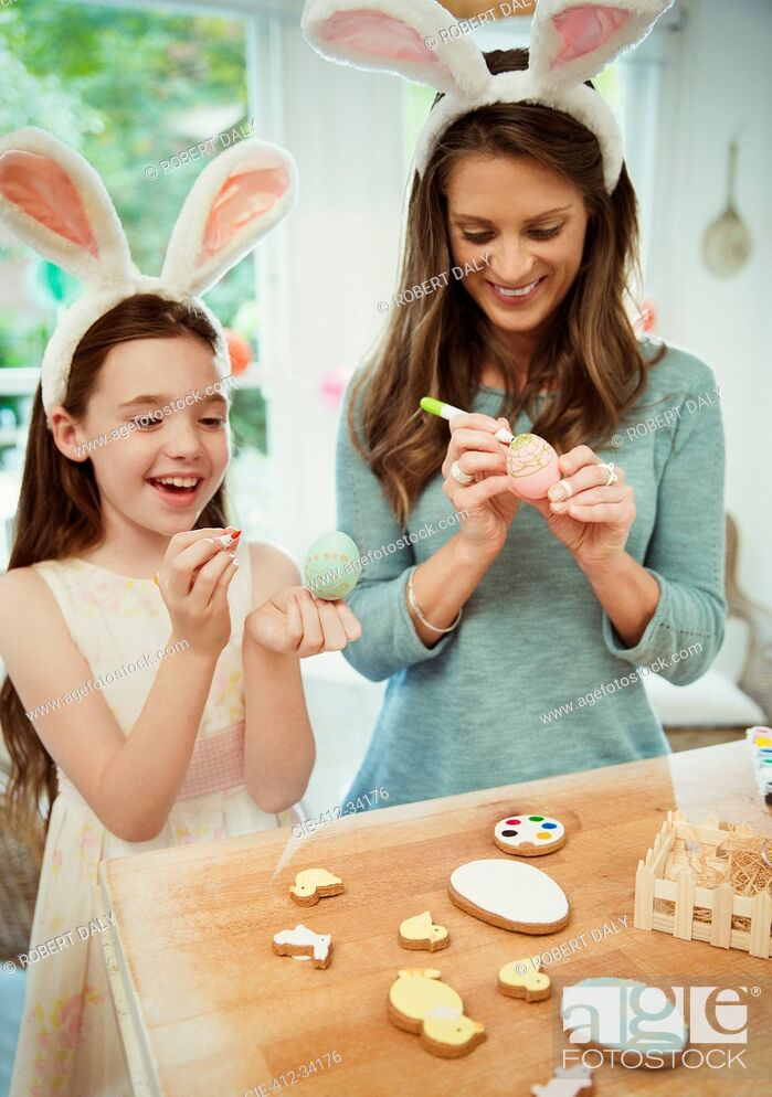 Stock Photo: Mother and daughter wearing costume rabbit ears decorating Easter eggs.