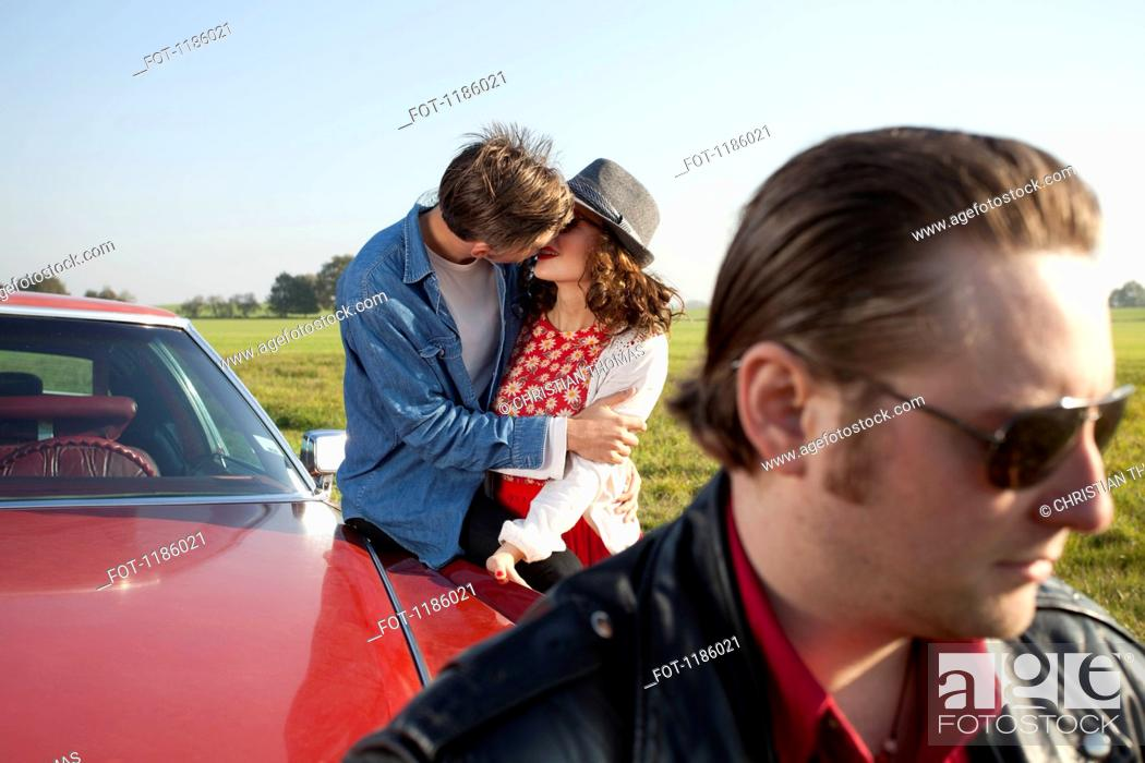 Stock Photo: A rockabilly couple kissing while leaning on a vintage car, man in foreground.