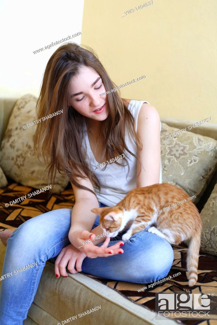 Stock Photo: Teen girl sitting on sofa at home with kitty.