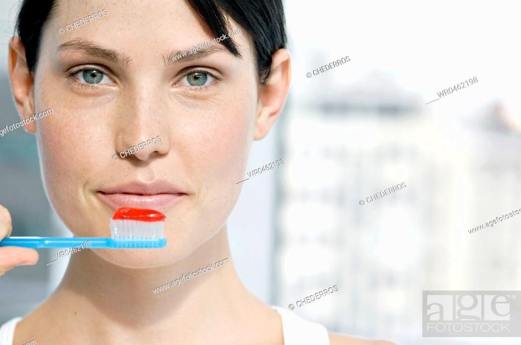 Imagen: Close-up of a young woman holding a toothbrush with toothpaste.