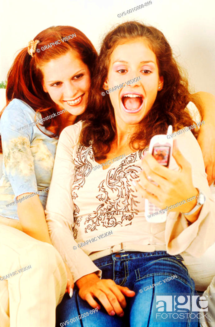 Stock Photo: Two young women sitting on sofa holding a mobile phone.