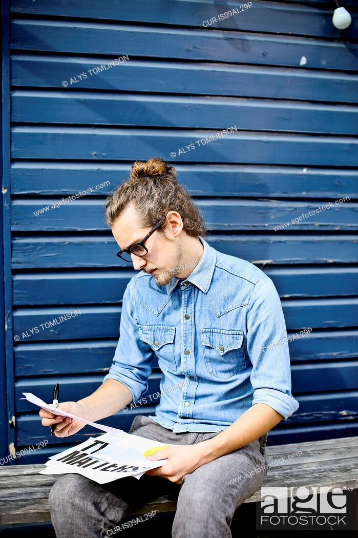 Imagen: Young man looking at print outs of designs outside.