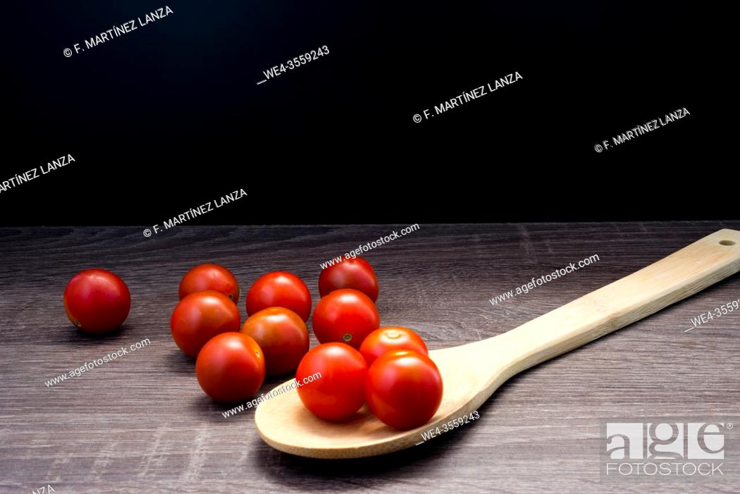 Stock Photo: Small cherri tomatoes with a wooden spoon on a table.